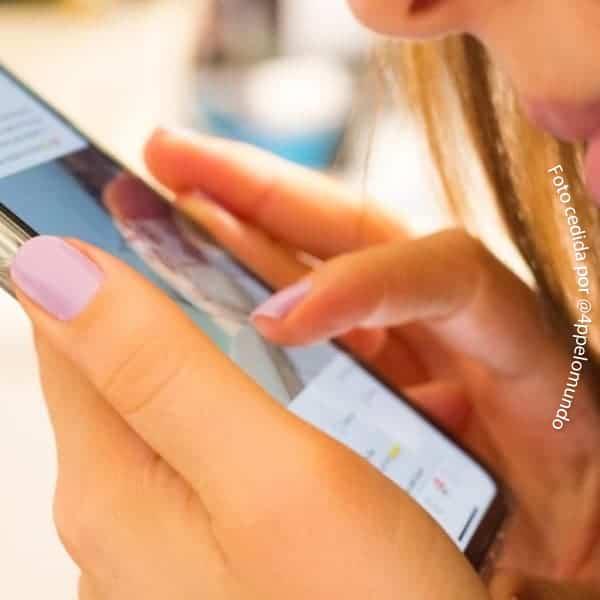 imagem de mãos de mulher segurando celular, ela toca a tela, usa esmaltes cor de rosa
