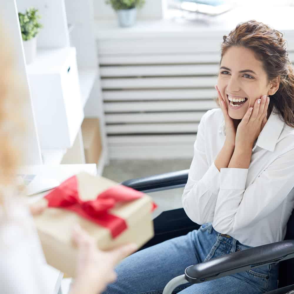 Mulher branca com deficiência física utilizando cadeira de rodas mostra expressão de surpresa. Uma pessoa oferece um presente embalado com um laço vermelho a ela.