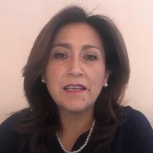 Retrato da Ana Arellano. Mulher com cabelos curtos e castanhos, está vestindo uma camiseta preta e colar e brincos de pérola.