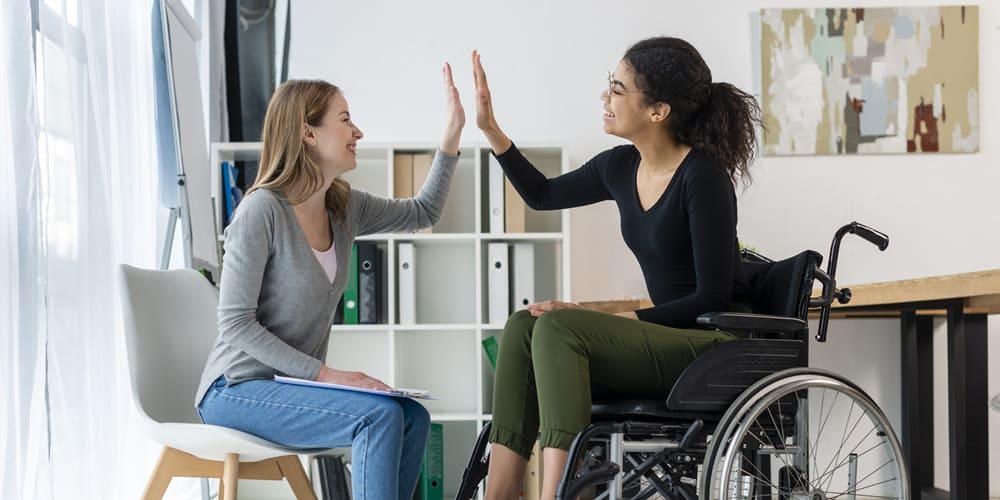Duas mulheres se cumprimentam batendo as mãos. Uma está sentada segurando uma prancheta, enquanto a outra, na cadeira de rodas sorri, em um fundo de escritório.