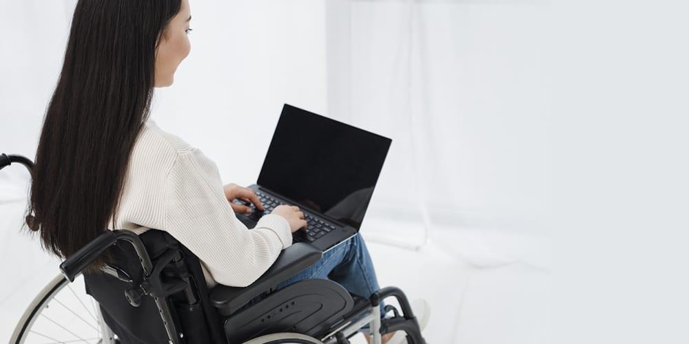 Em um fundo branco, mulher com deficiência física, em cadeira de rodas, segura um notebook aberto.