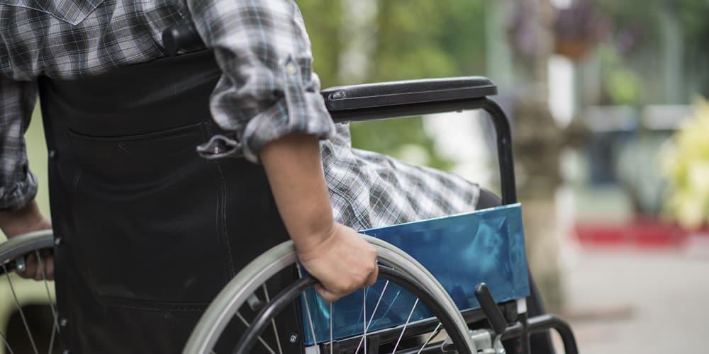 Foco na parte inferior das costas de um mulher em cadeiras de rodas com blusa quadriculada. Fundo desfocado.