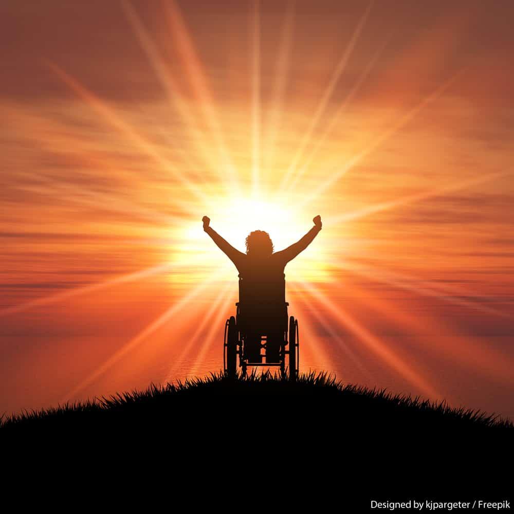 Pessoa em cadeira de rodas em um campo levanta os braços em sinal de vitória, atrás, o sol faz sombra na imagem.