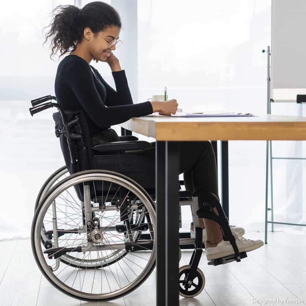 Mulher negra com deficiência física está utilizando a cadeira de rodas enquanto escreve em uma mesa de madeira, fundo branco.