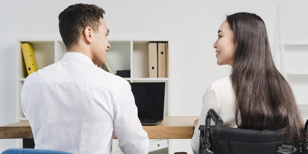 De costas, um homem sentado ao lado de uma mulher com cadeira de rodas, apoiados em uma mesa de madeira com um fundo de ambiente de escritório.